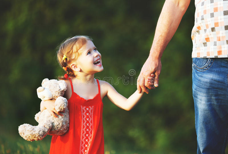 Father`s day. Child girl hugging father in nature at sunset. In summer royalty free stock images