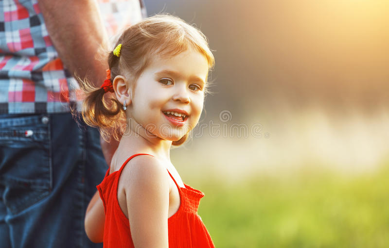 Father`s day. Child girl hugging father in nature at sunset. In summer stock photography