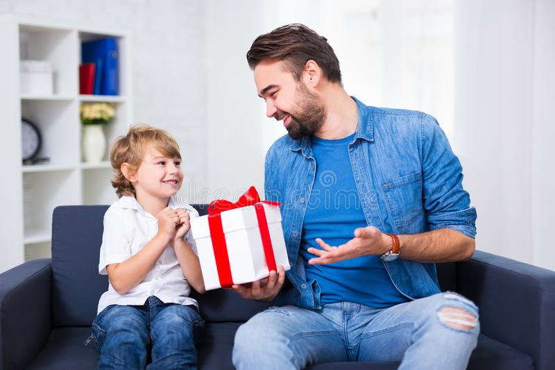 Father`s day or christmas concept - little son and his father wi. Th gift at home stock photography
