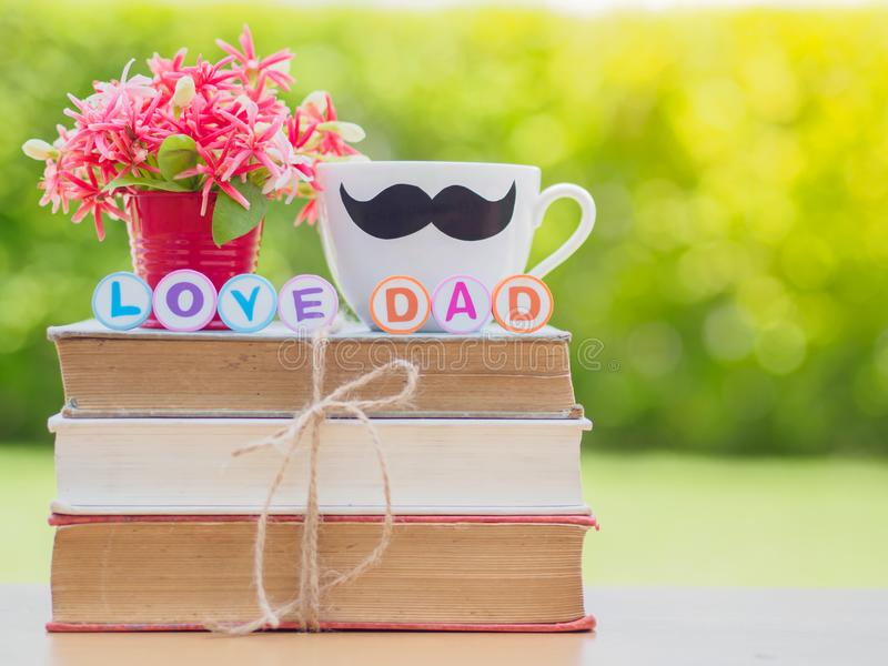 Father`s day concept. LOVE DAD alphabet on stack of books, gifts, tea cup with black Mustache and flower on background stock images