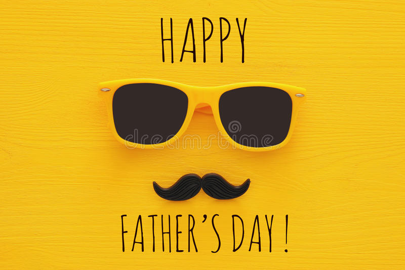 Father& x27;s day concept. Hipster yellow sunglasses and funny moustache. On wooden background stock photos