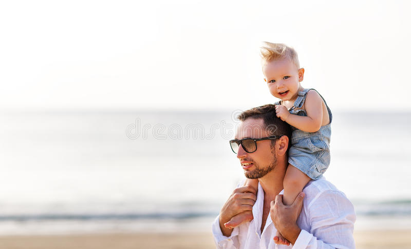 Father`s day. Dad and baby son playing together outdoors on a su. Mmer beach stock photo