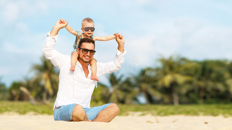 Father`s day. Dad and baby son playing together outdoors on a su. Mmer beach stock photos