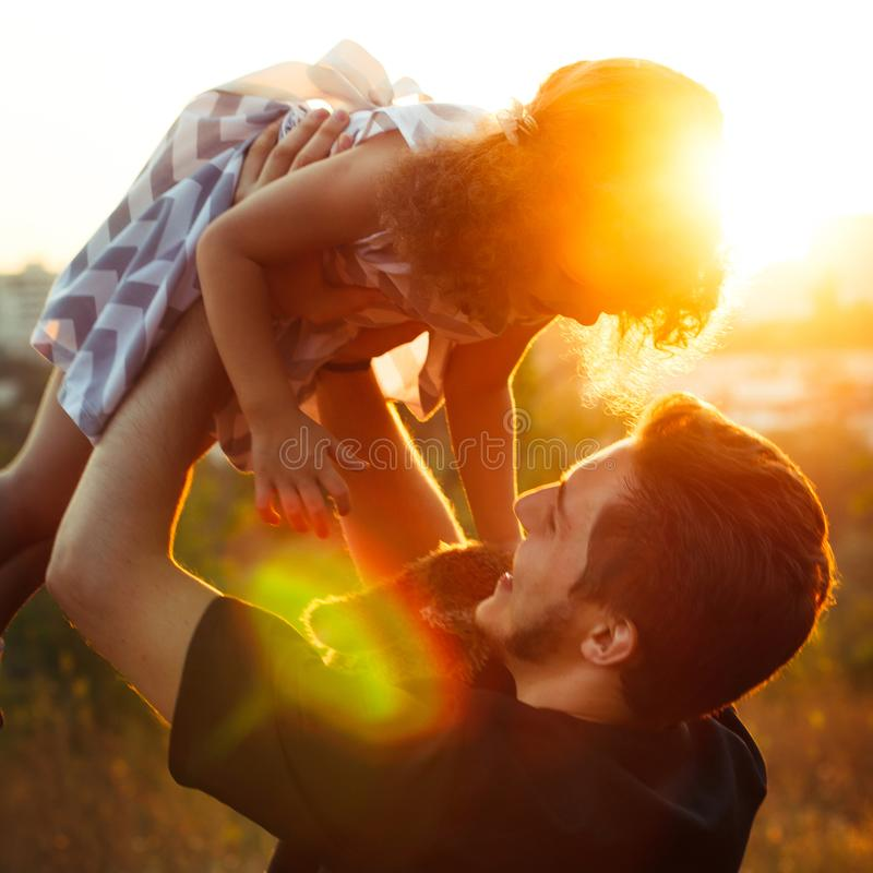 Father`s day. Dad and child daughter playing together outdoors on a summer park. Sunny evening. Square photo royalty free stock photography