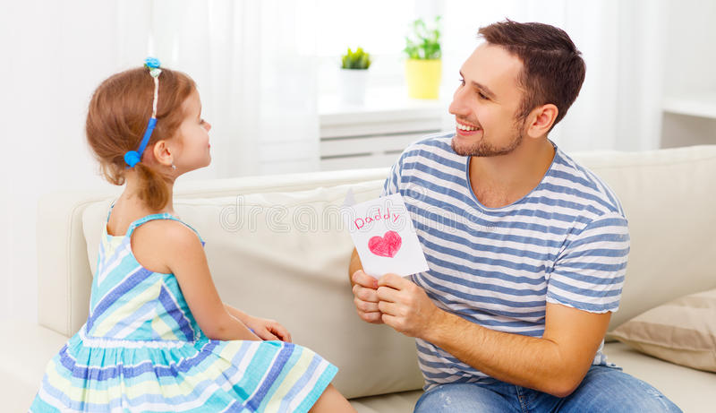Father`s day. Happy family daughter giving dad greeting card stock photography