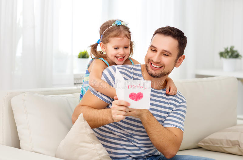 Father`s day. Happy family daughter giving dad greeting card. Father`s day. Happy family daughter giving dad a greeting card on holiday royalty free stock image