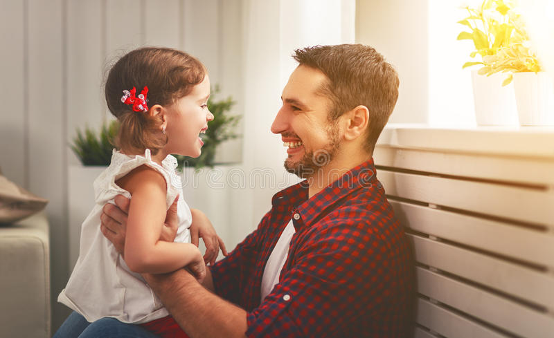 Father`s day. Happy family daughter hugging dad and laughs. On holiday royalty free stock images