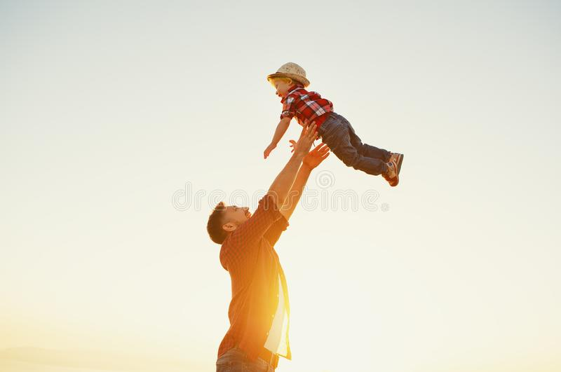Father`s day. Happy family father and toddler son playing and la. Ughing on nature at sunset stock photography