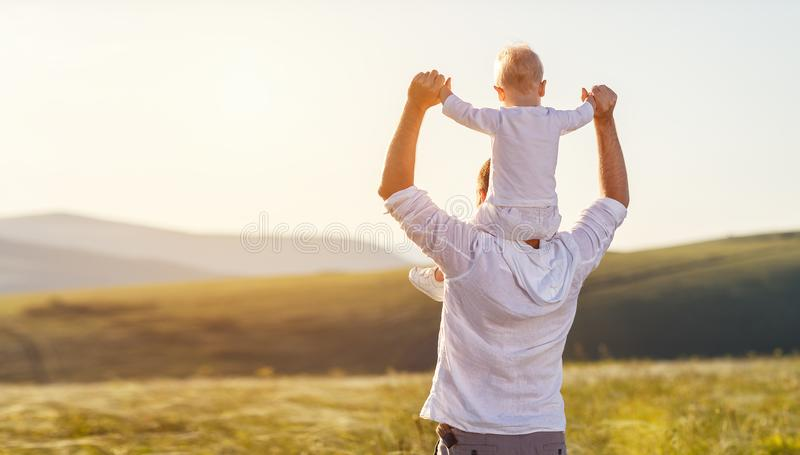 Father`s day. Happy family father and toddler son playing and l. Aughing on nature at sunset royalty free stock photos