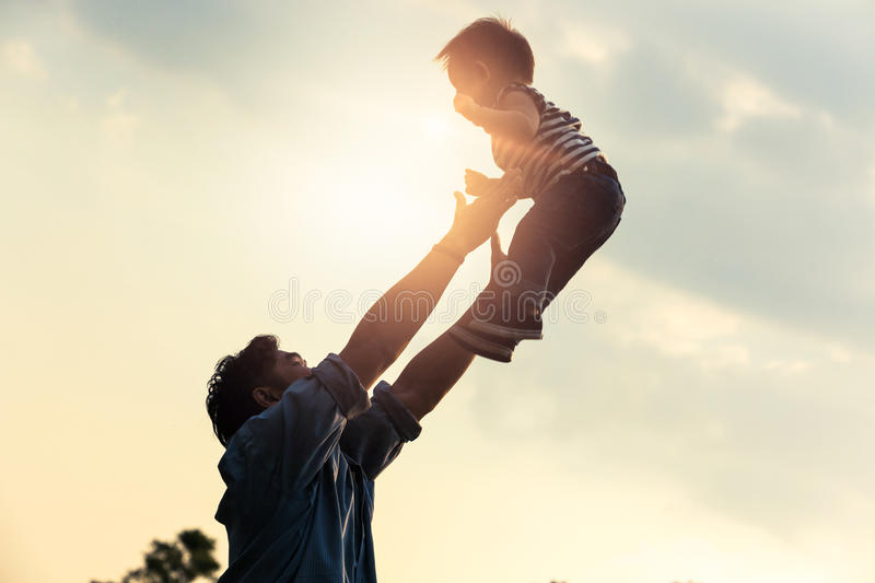 Father`s day. Happy joyful father having fun throws up in the ai. R child royalty free stock image