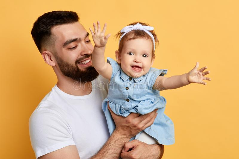 Father`s day. smiling father looking at his adorable daughter. Who is looking at the camera and raising her arms. close up photo. isolated yellow background stock photography
