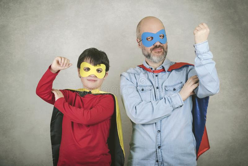 Father`s day,father and son dressed as a superhero. Against gray background royalty free stock photos
