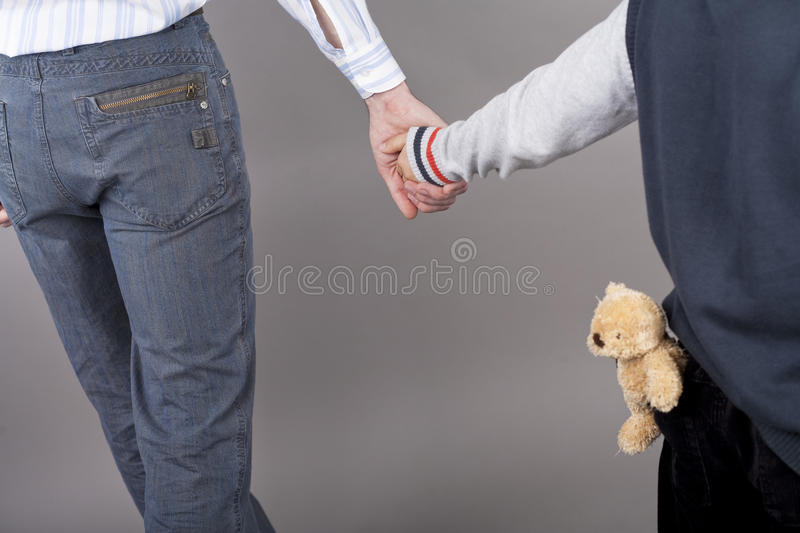 Father's protection. Young and careful father together with his teenager son holding hands of each other standing isolated over gray background with teddy bear stock photo