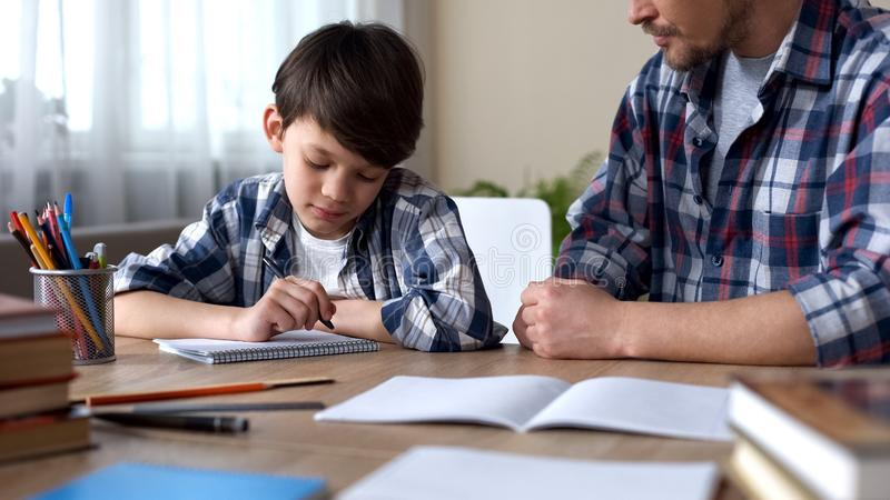 Father scolding son, making him to do homework, boy beginning to write task stock photography