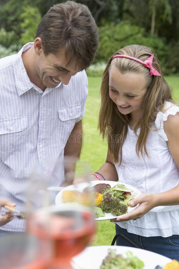 Father serving daughter from barbecue stock image