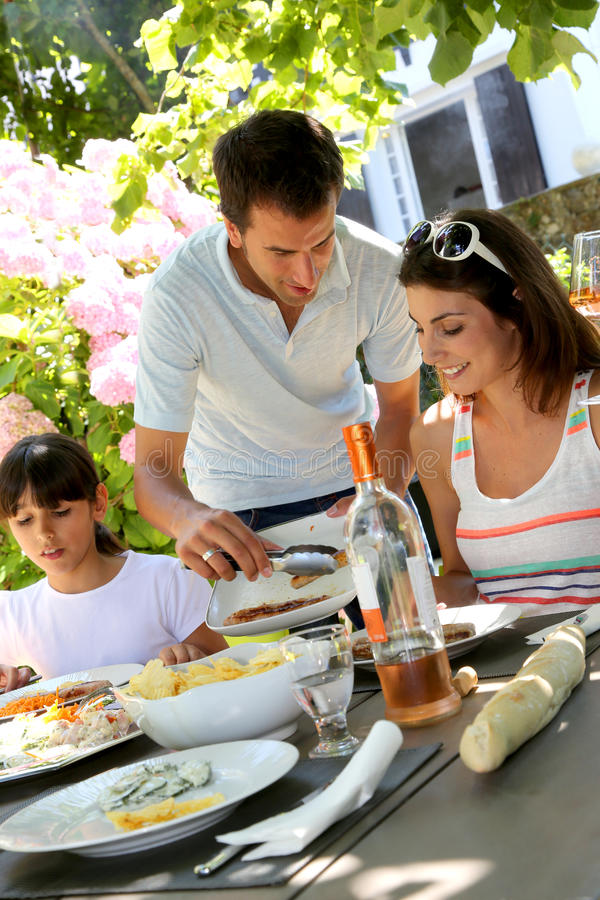 Father serving meat from barbecue stock photography