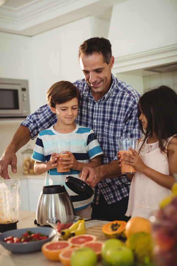 Father serving smoothie to his kids in kitchen stock photos