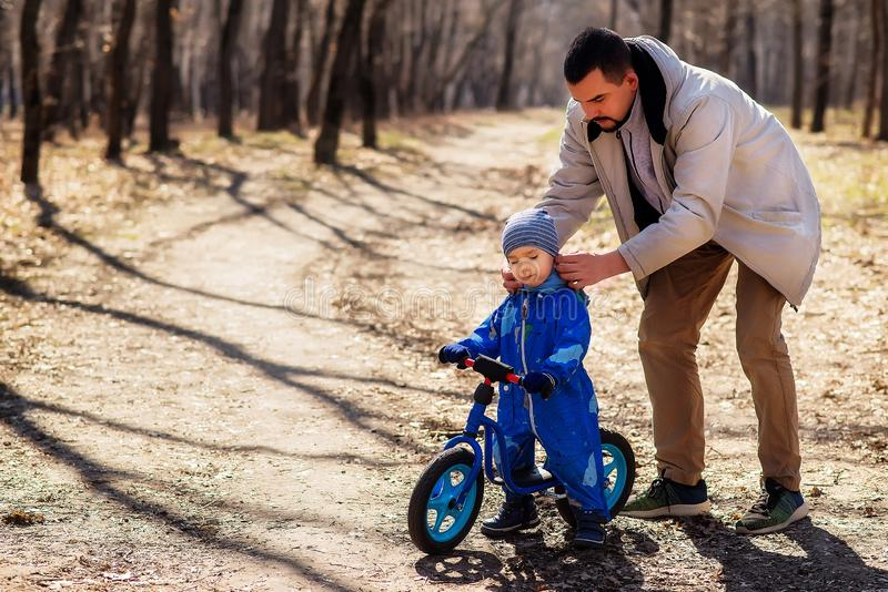 Father setting a cap to his toddler son in blue jumpsuit in the park. The child is sitting on a blue balance bike stock photography