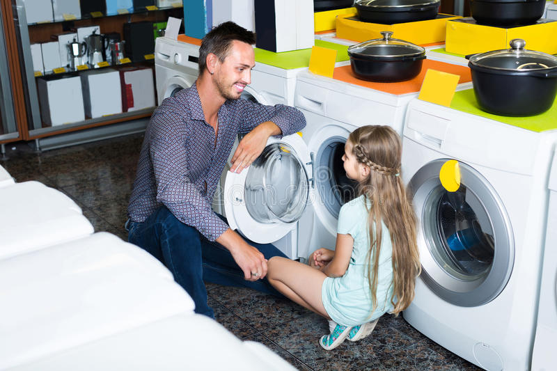 Father shopping goods in home appliance store with his daughter royalty free stock photography