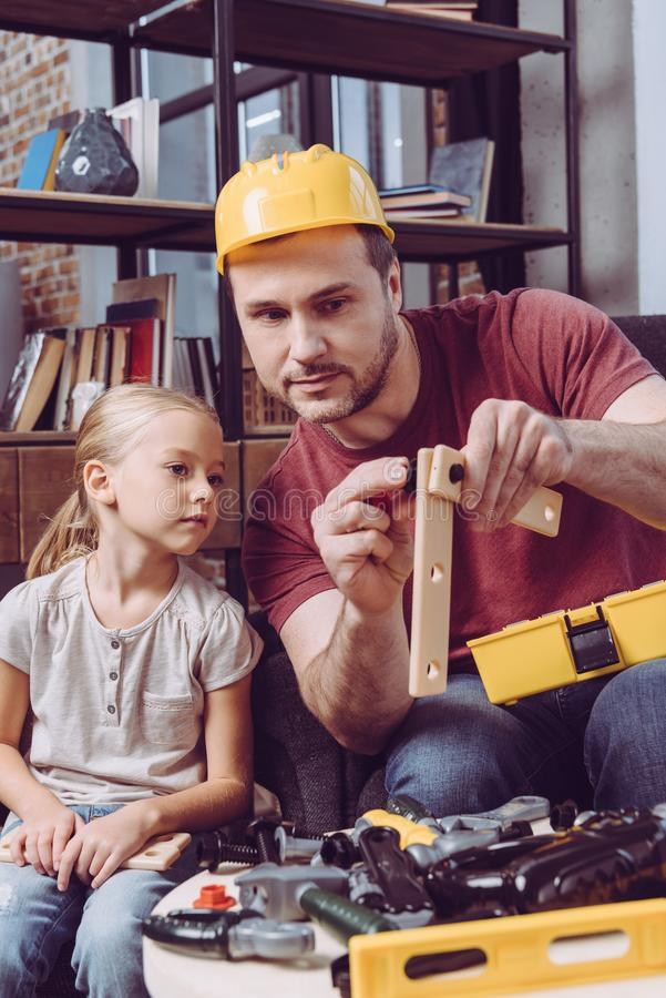 Father showing his daughter how to make a wooden frame with different toy tools at home stock photography