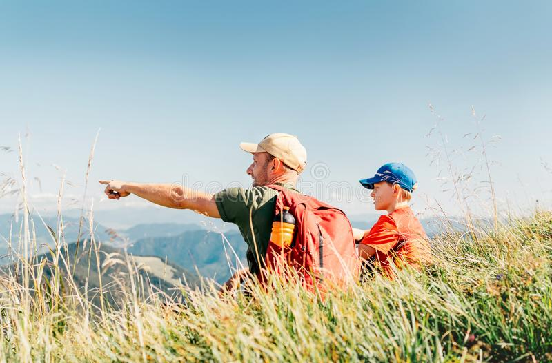 Father showing something interesting to his teenager son sitting on the grass during their mounting hiking walking stock photography