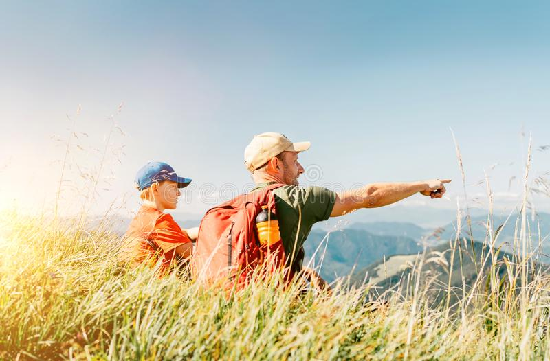 Father showing something interesting to his teenager son sitting on the grass during their mounting hiking walking royalty free stock images