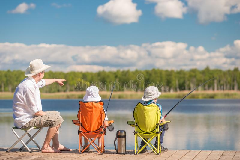 Father shows his children the place of biting fish on the lake, stock photos