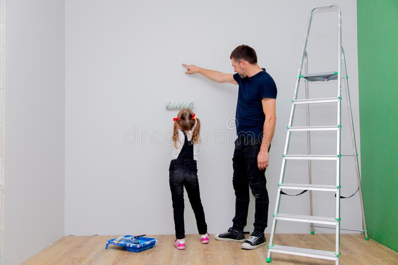 Father shows his daughter how to paint royalty free stock photo