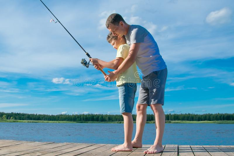 Father shows his son on the pier how to hold a fishing rod to catch fish, against the blue lake and sky royalty free stock image