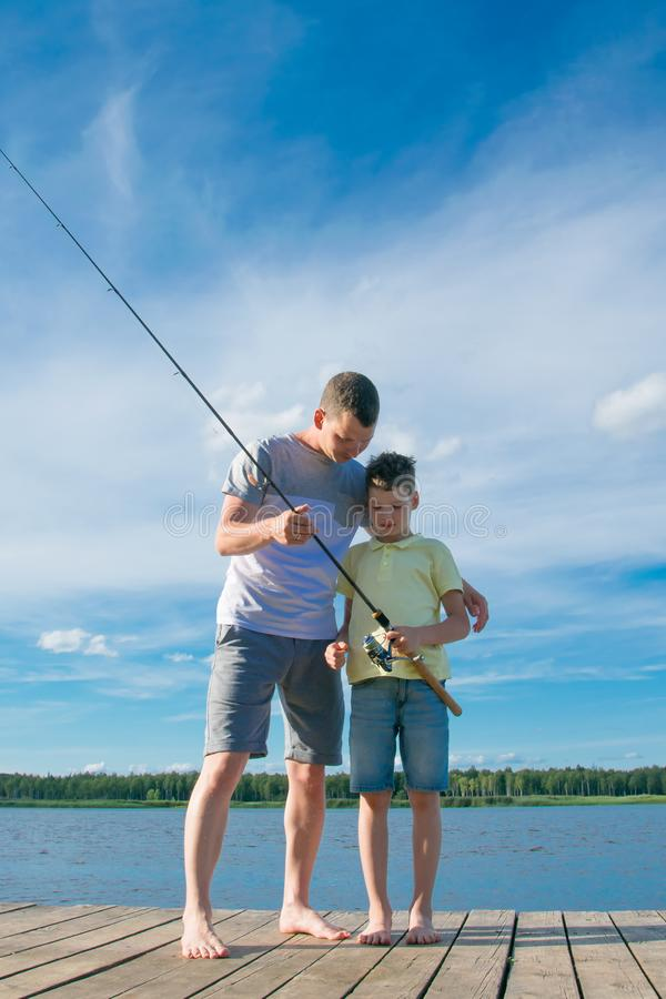 Father shows his son on the pier how to keep spinning to catch fish, against a beautiful landscape royalty free stock photography
