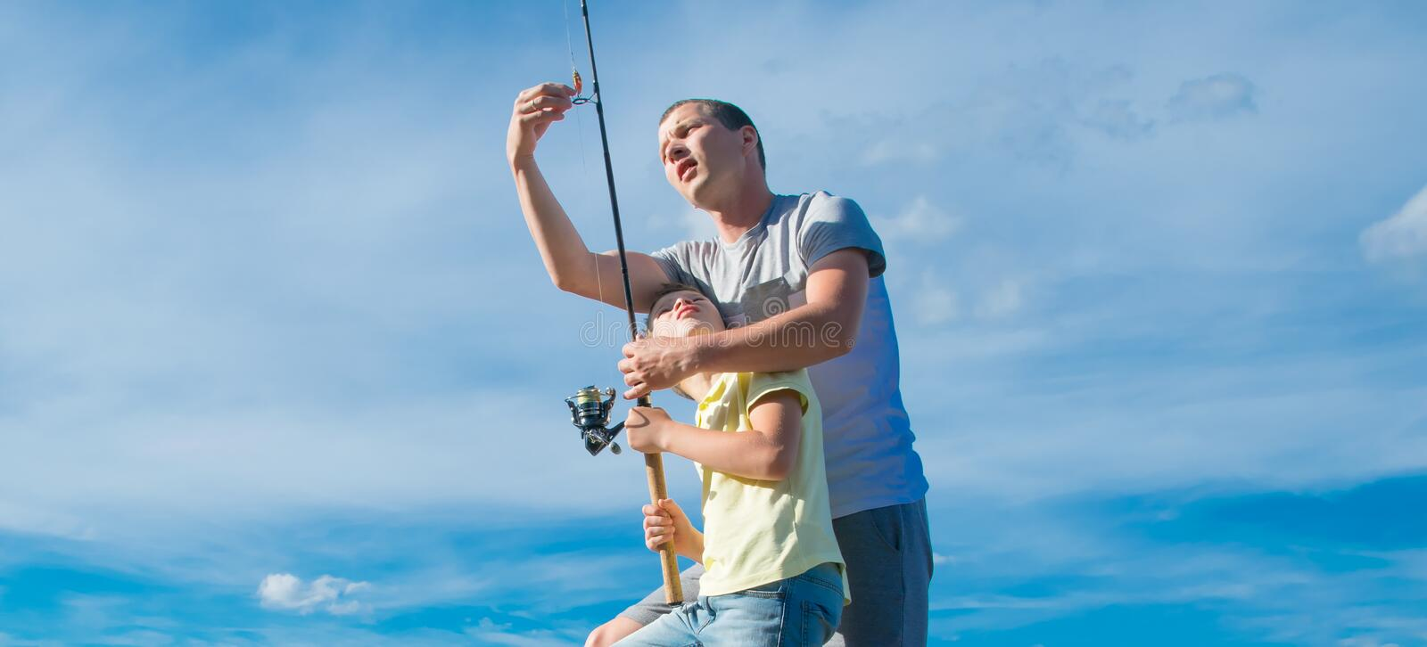 The father shows his son on the pier, how to set up a fishing rod to catch fish, against the blue sky, close-up stock image