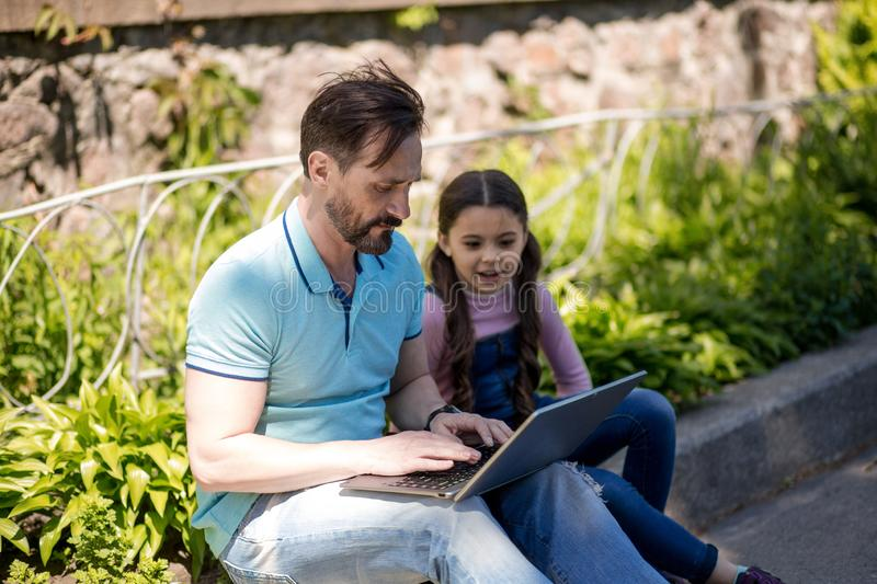 Father Siting Together With His Daughter And Looking On The Laptop Outdoors. stock photo