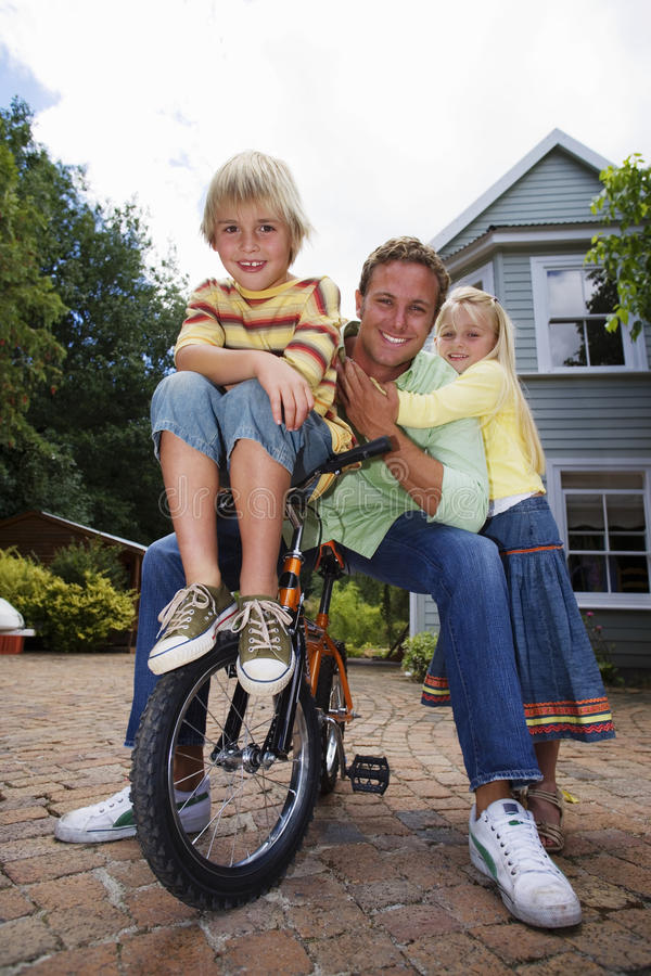 Father sitting on bicycle with children (4-6) in driveway, smiling, front view, portrait stock photography