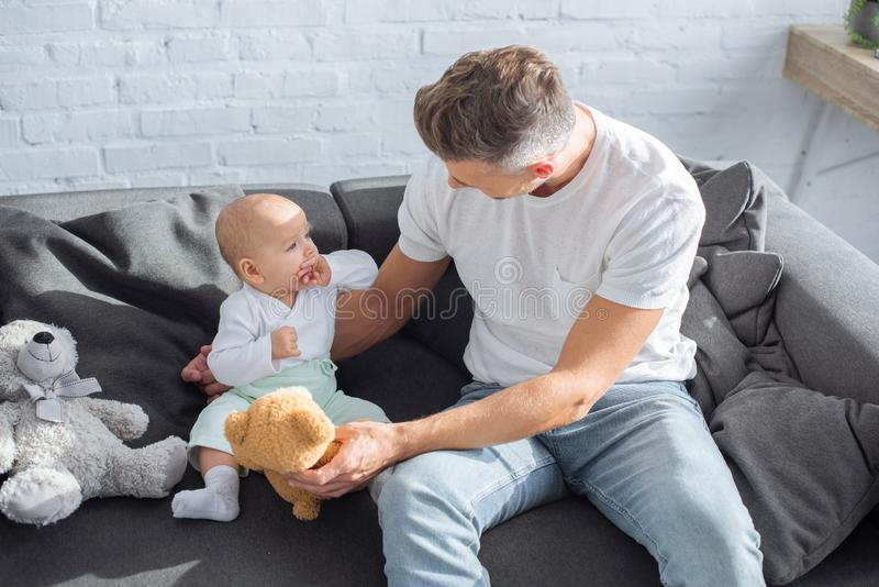 Father sitting on couch with baby daughter and playing with teddy bears. At home royalty free stock image