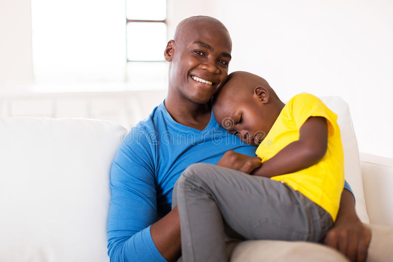 Father sitting couch son. Loving father sitting on the couch with his cute son royalty free stock photos