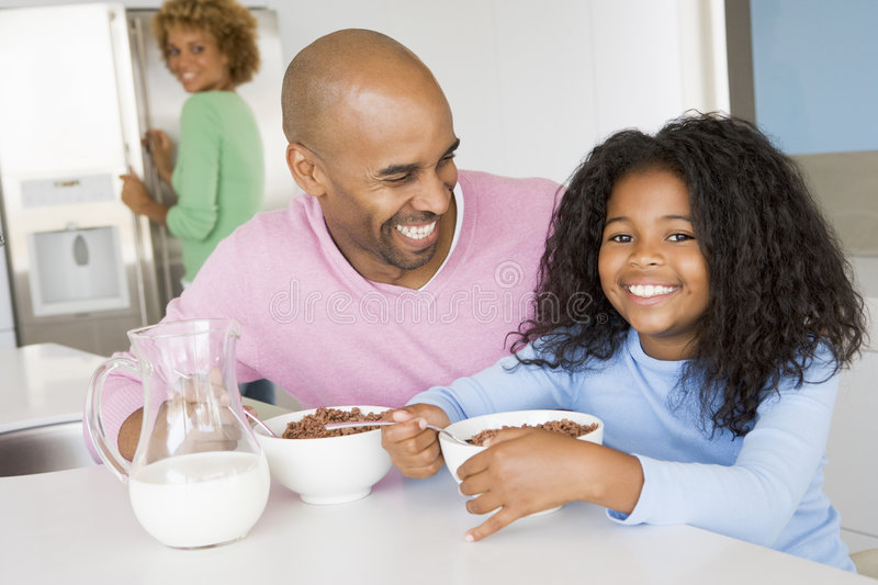 Father Sitting With Daughter at Breakfast With Her. Father Sitting With Daughter As She They Eat Breakfast With Her stock photo
