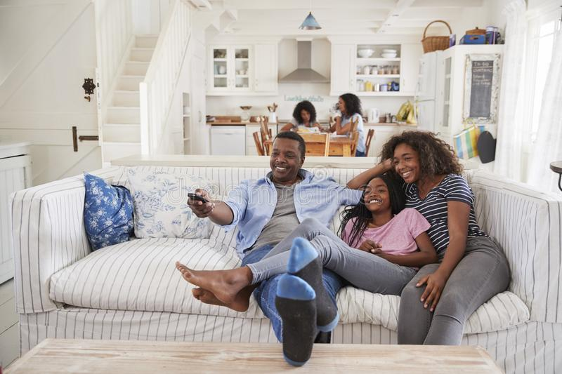 Father Sitting On Sofa Watching TV With Teenage Daughters royalty free stock photo