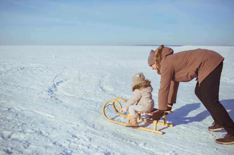 Father sledges his little daughter in winter stock images