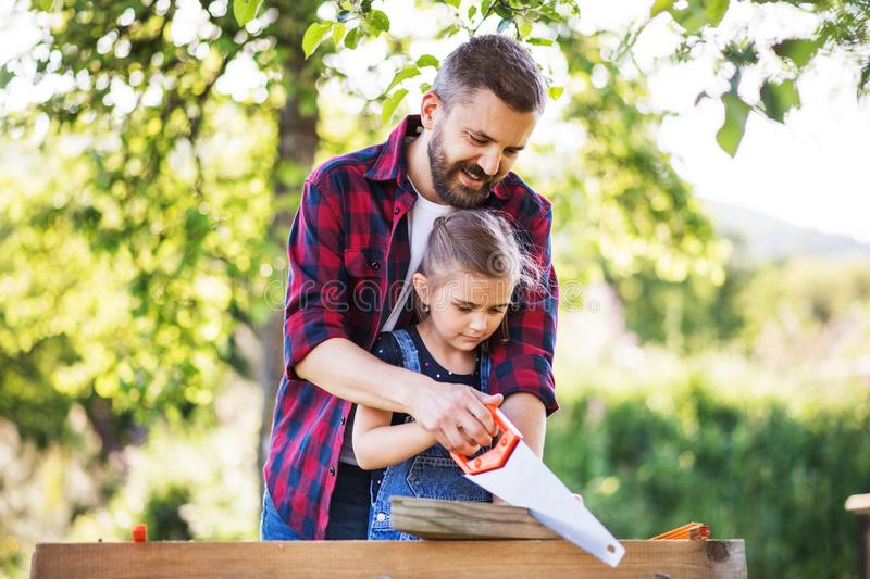 Father with a small daughter outside, making wooden birdhouse. stock photos