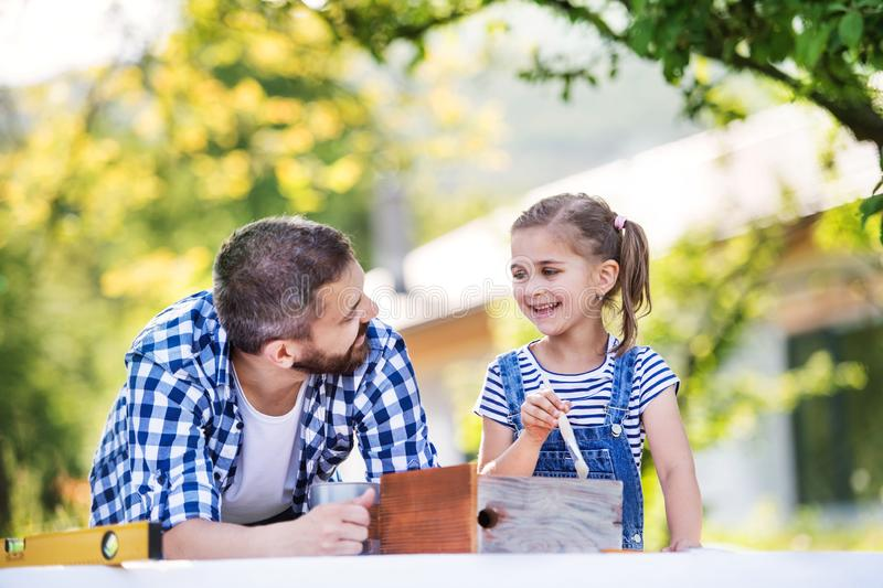 Father with a small daughter outside, painting wooden birdhouse. stock image