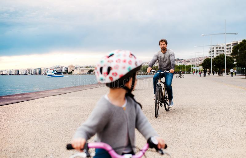 Father and small daugther with bicycles outdoors cycling on beach. A father and small daugther with bicycles outdoors cycling on beach royalty free stock photography