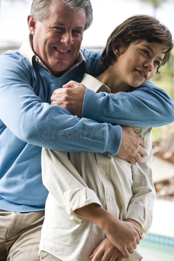 Father and son. Father giving son a bear hug stock photography