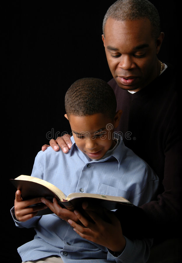 Father and Son. Reading a Bible over a black background