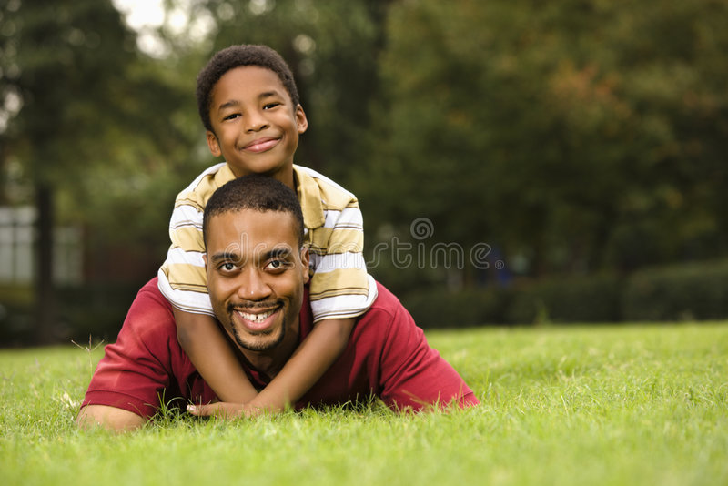 Father and son. Father lying in grass smiling as son climbs on his back and hugs his neck