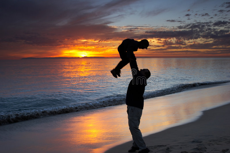 Father and son. Playing together on a beach at sunset