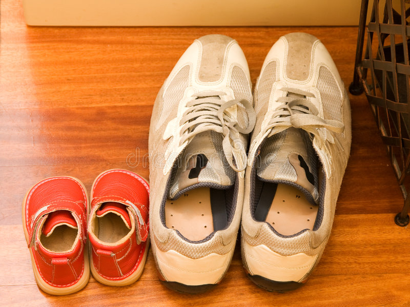 Father and son. Shoes comparative stock image
