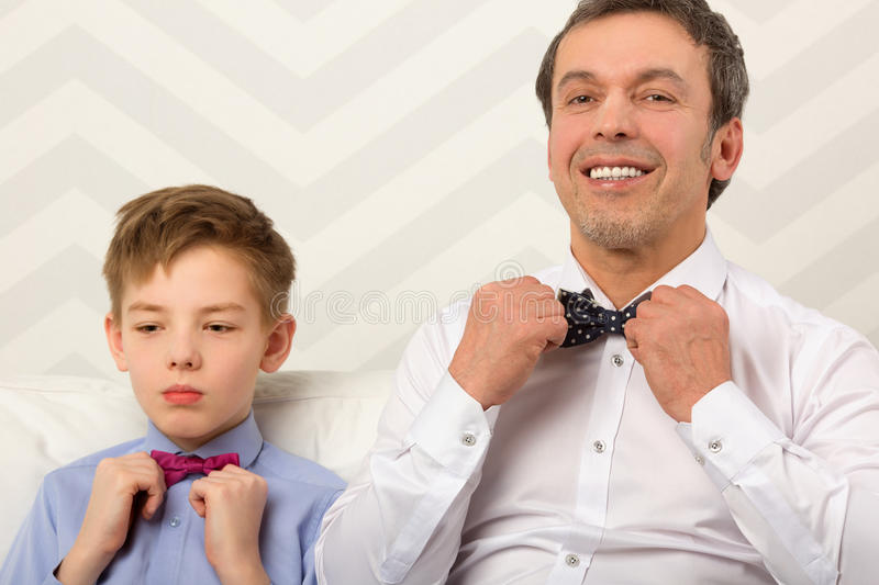 Father and son adjusting bowties royalty free stock images