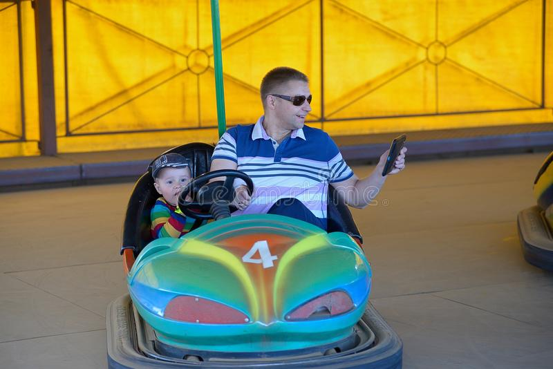 Father and son in amusement park ride on car.  stock images