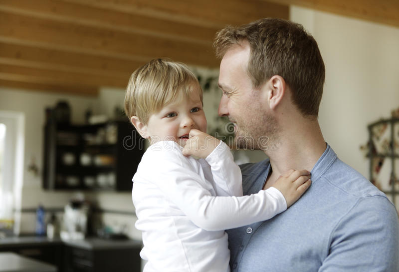 Father with son on the arm. A father holding his son at home in the living room on the arm royalty free stock photos