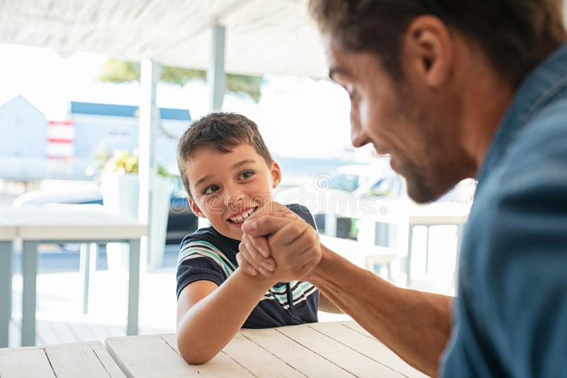 Father and son in arm wrestling competition. Happy father and smiling boy arm wrestling for fun. Man competing in arm wrestling with cheerful young child outdoor stock image